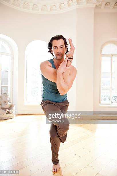 Man in sunny yoga studio holding twisted pose