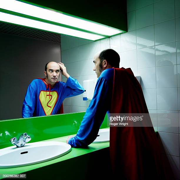 man in superhero costume looking at reflection in mirror - 鏡 物品 個照片及圖片檔