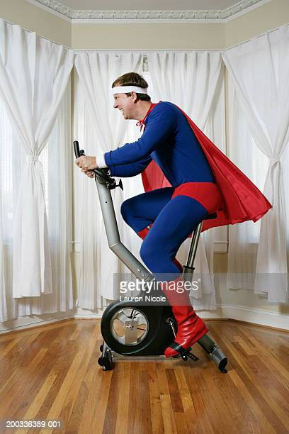 Man in superhero costume on exercise bike, side view