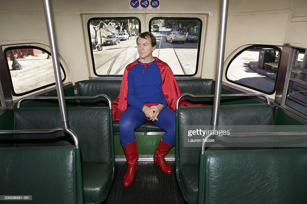Man in superhero costume riding bus, hands clasped : Stock Photo