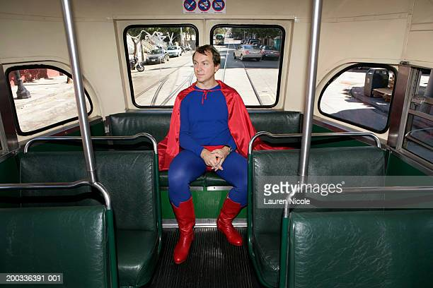 Man in superhero costume riding bus, hands clasped