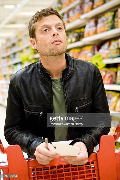 Man in supermarket with shopping list