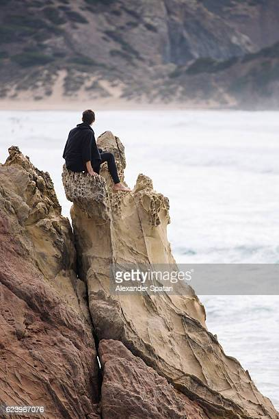 Man in surf wetsuit sitting on the edge of a cliff and looking out over ocean