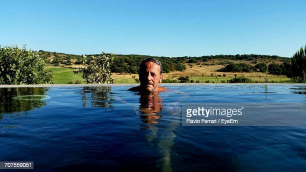 Man In Swimming Pool By Landscape Against Clear Blue Sky