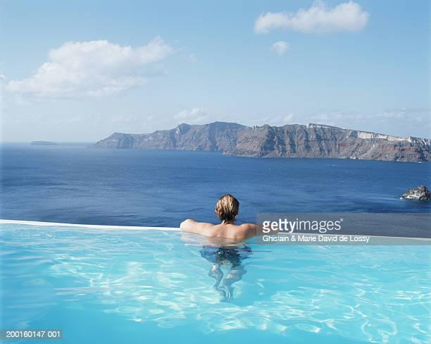 Man in swimming pool by ocean, rear view