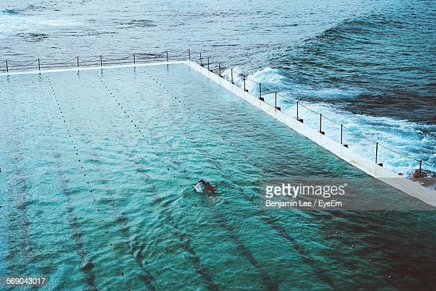 Man In Swimming Pool With Calm Sea In Background