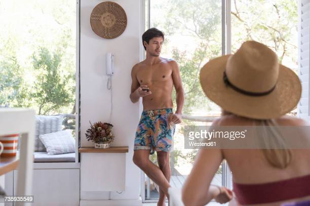 Man in swimming shorts holding cell phone with woman in background
