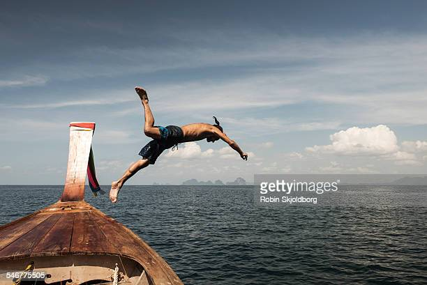 Man in swimming trunks diving from Longtail boat