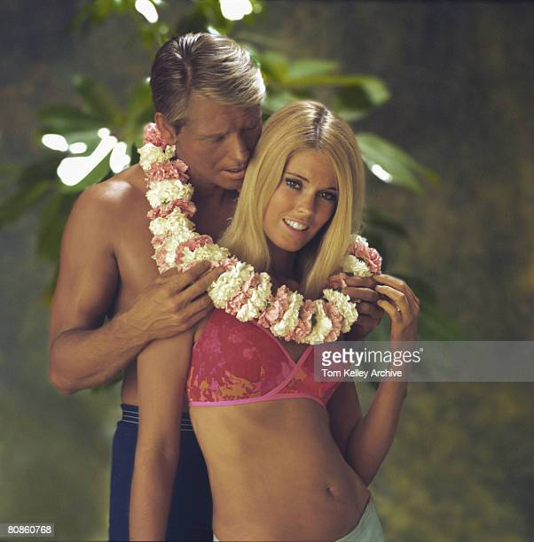 Man in swimming trunks embraces a woman in a bikini as a lei encircles their necks mid1970s