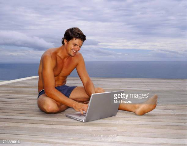 A man in swimming trunks sitting on a deck by the ocean, working on a laptop.