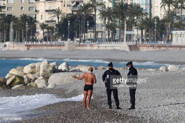 Man in swimsuit chats with two French policemen on the beach in Nice, on the French riviera during the first weekend lockdown put in place by...