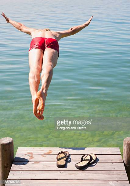 Man in swimsuit jumping into lake