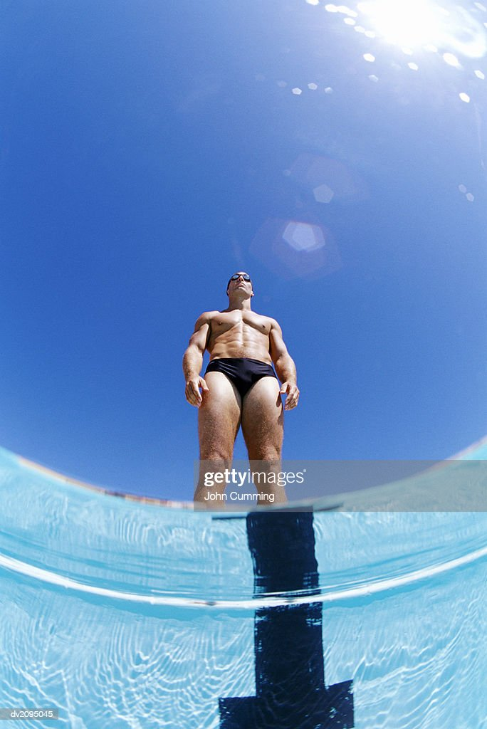 Man in Swimwear Standing at Poolside : Stock Photo