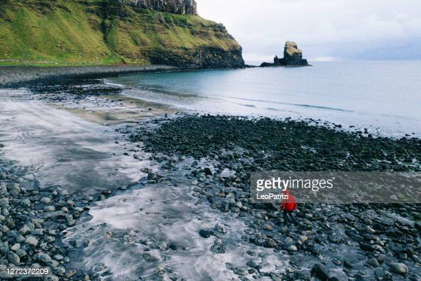 man in talisker bay beach in scotland, uk - western isles stock pictures, royalty-free photos & images