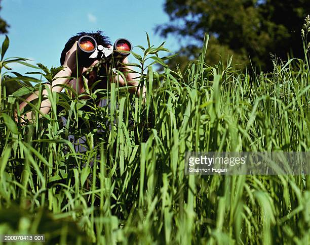 man in tall grass looking through binoculars - appearance stock pictures, royalty-free photos & images