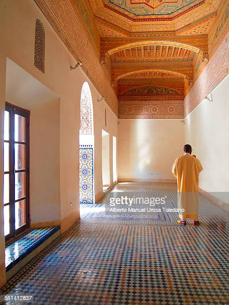 Man in the Badia Palace,this room is decorated with a beautiful tiled floor and a spectacular work in the ceiling. It was taken in Marrakesh, Morocco.