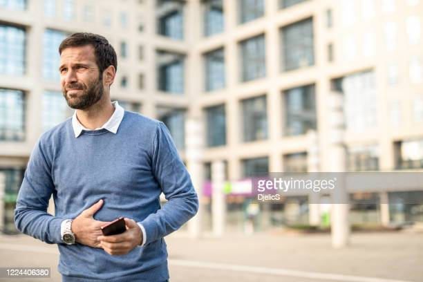 man in the city having stomachache. - human intestine stock pictures, royalty-free photos & images