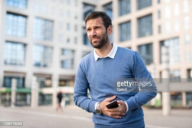 man in the city having stomachache. - refluxo gastro esofágico imagens e fotografias de stock