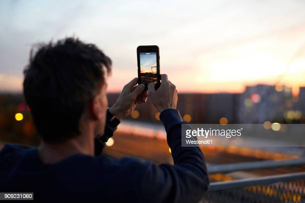 man in the city taking cell phone picture in the evening - fotografie stock-fotos und bilder