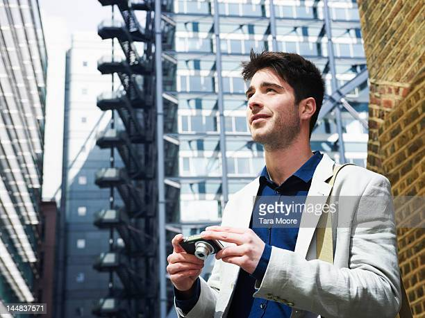 man in the city with camera and smiling - newtechnology stock pictures, royalty-free photos & images