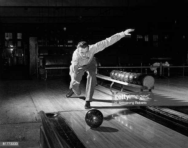 Man In The Classic Pose After Releasing The Ball Down The Polished Wooden Bowling Lane With The Rack & Spare Balls In The Background.