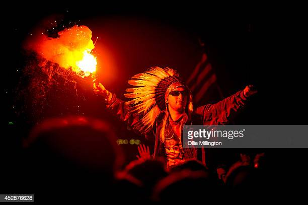 A man in the crowd wearing a Native American Headdress holding a lit flare as Jake Bug performs headlining The Other stage at the end of Day 2 of The...