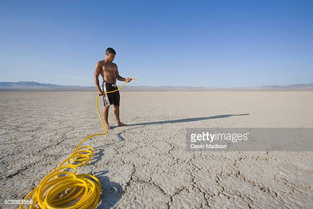 Man in the Desert Holding Garden Hose