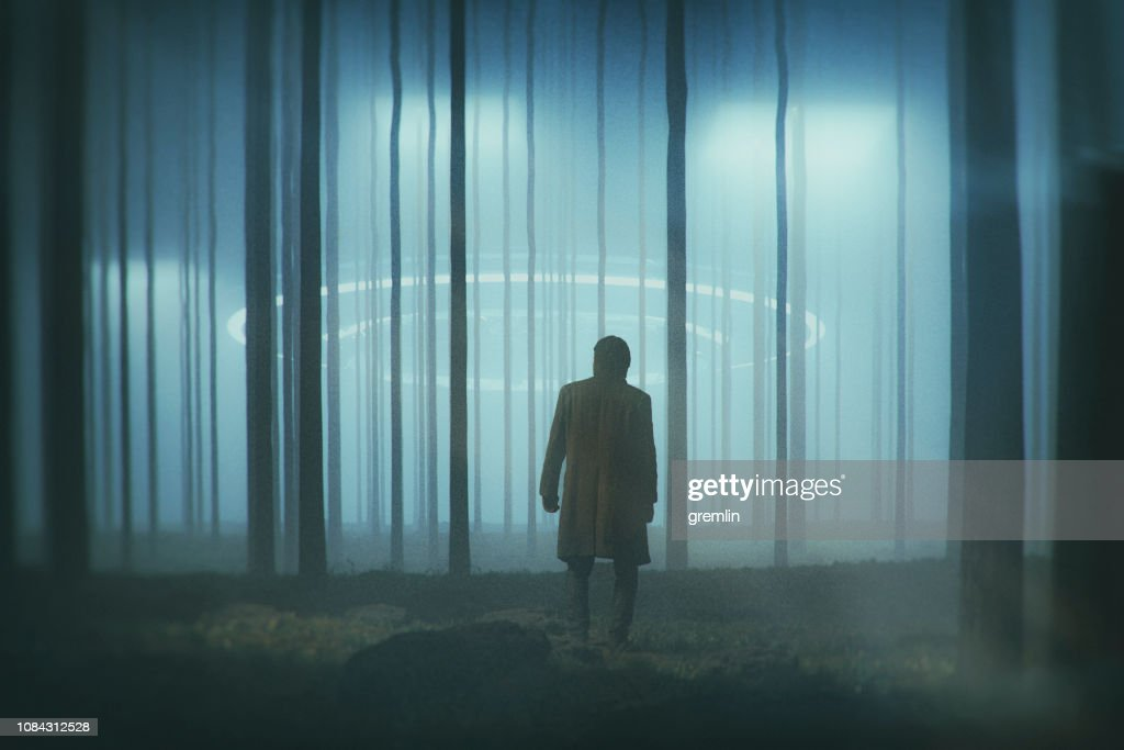 Man in the forest at night with landing UFO : Stock Photo
