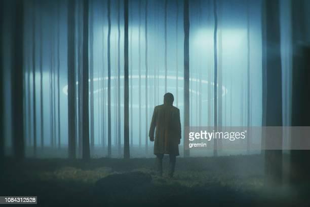 homem na floresta à noite com o pouso de ufo - disco voador - fotografias e filmes do acervo