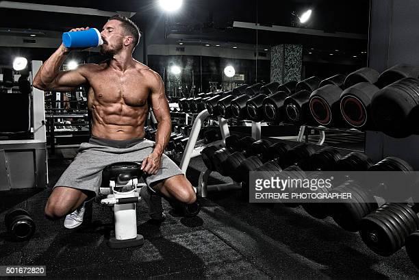 Homem no ginásio beber proteína bebida de batidos