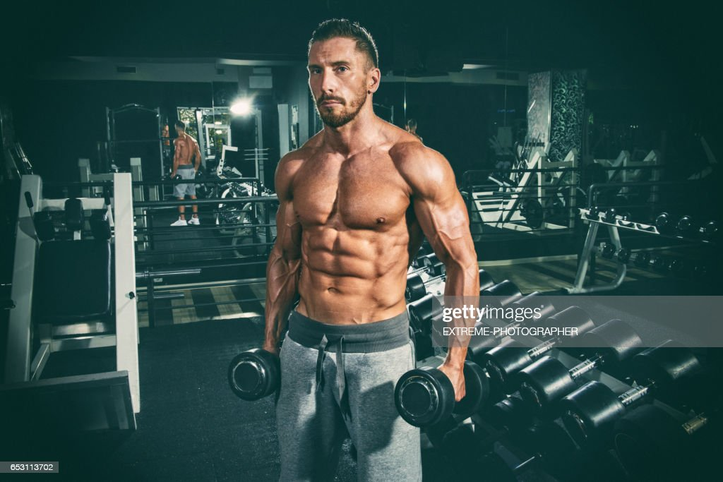 Man in the gym exercising with dumbbells : Stock Photo