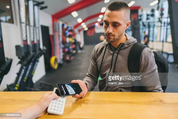 man in the gym paying with digital wallet - serving sport stock pictures, royalty-free photos & images