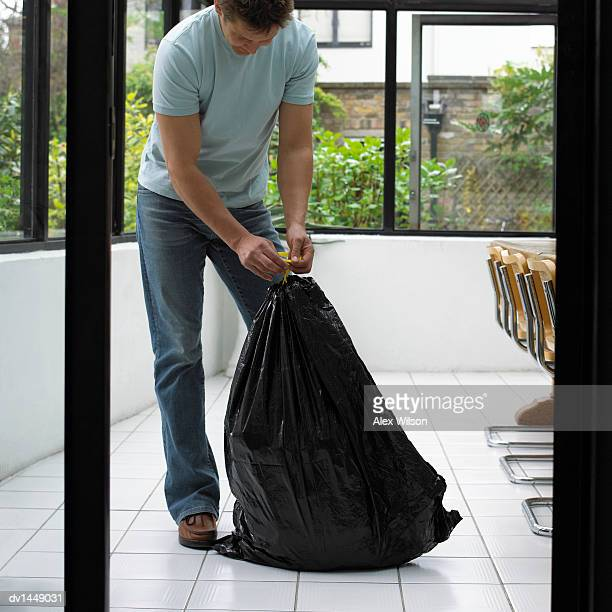 man in the home tying a bin bag - man tied to chair stock photos and pictures