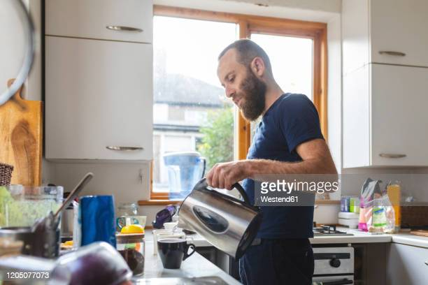 man in the kitchen preparing a tea - making stock pictures, royalty-free photos & images