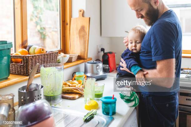 man in the kitchen preparing food and cuddling his son - carrying stock pictures, royalty-free photos & images