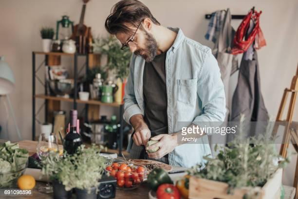Mann in der Küche und bereitet Papaya-Salat