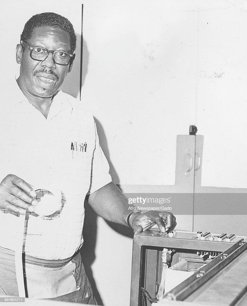 A man in the newspaper offices of the Afro American newspaper, holding the tape for a typesetting device, Baltimore, Maryland, 1948.