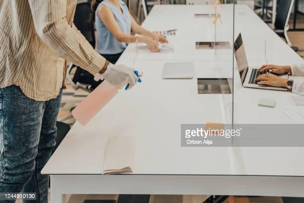 homem no escritório usando desinfetante para higienizar superfície monitor durante a pandemia covid-19 - grupo pequeno de pessoas - fotografias e filmes do acervo