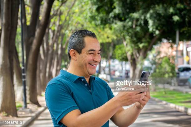 man in the park watching cell phone - mid adult men stock pictures, royalty-free photos & images