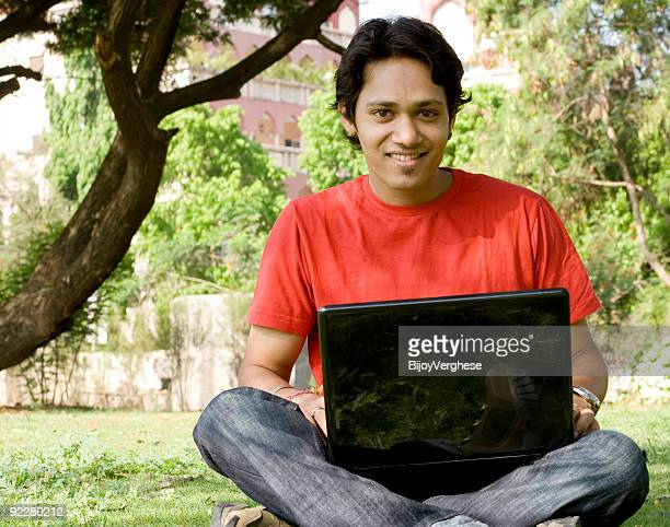 A man in the park working with a laptop