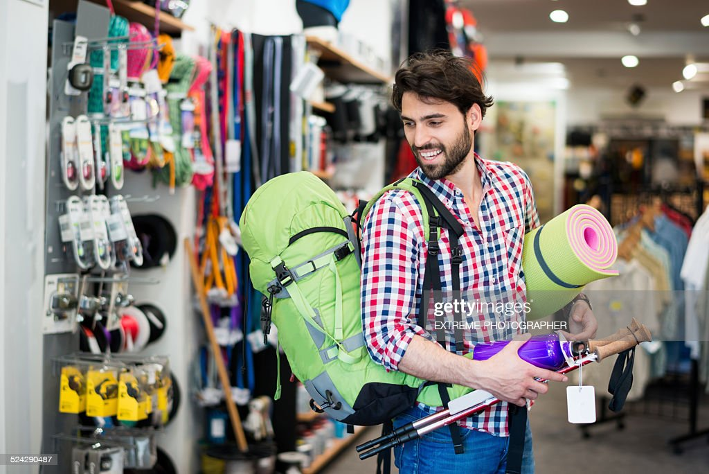 Man in the store buying camping equipment : Stock Photo