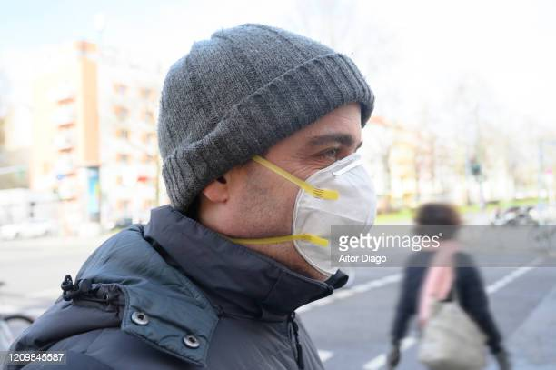 man in the street wearing a protection mask looking at something. unrecognizable persons in the background. berlin, germany. - 1918 flu pandemic stock pictures, royalty-free photos & images