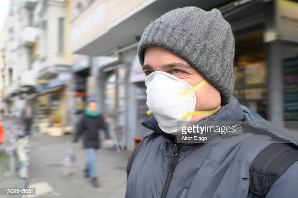 man in the street wearing a protection mask looking at something. berlin, germany. - 1918 flu pandemic stock pictures, royalty-free photos & images