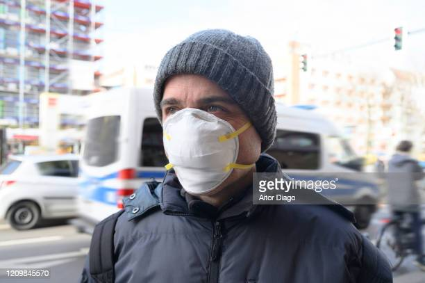 man in the street wearing a protection mask. there's a police car out of focus in the background. berlin, germany. - 1918 flu pandemic stock pictures, royalty-free photos & images