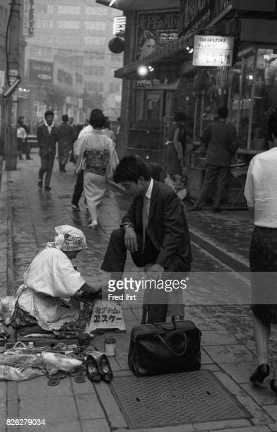 A man in the streets of Tokyo is getting his shoes shined Japan 1963