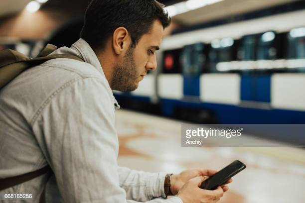 Man in the subway station using smart phone