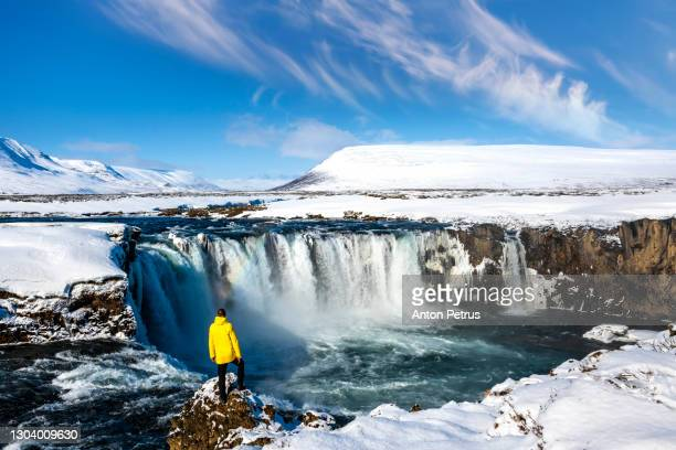 man in the yellow jacket on the background of godafoss waterfall in the winter at dawn. - iceland stock pictures, royalty-free photos & images