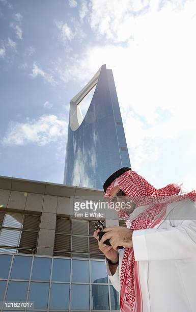 man in thobe using mobile phone, kingdom tower, riyadh, saudi arabia - riyadh stock pictures, royalty-free photos & images