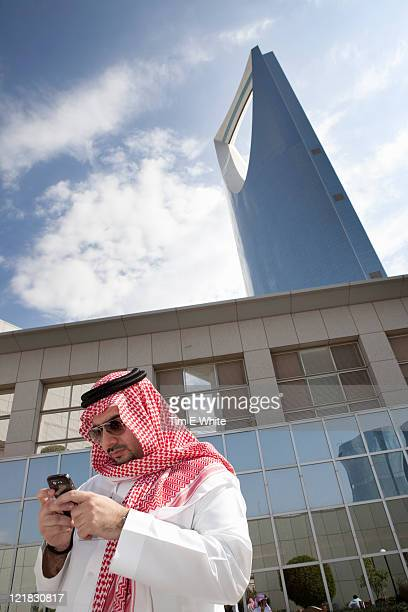 Man in Thobe using mobile phone, Kingdom Tower, Riyadh, Saudi Arabia