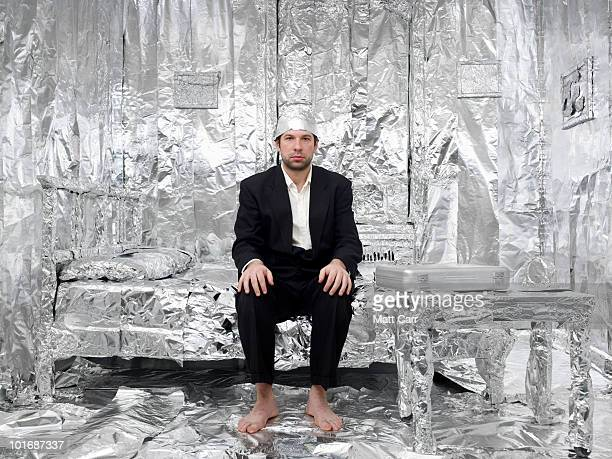 man in tin foil lined bed room - hat stock pictures, royalty-free photos & images